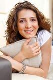 Portrait eines lächelnden Mädchens, das ein Kissen anhält Stockfotos
