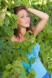 Portrait eines Mädchens in den Blättern der Traube Stockbilder