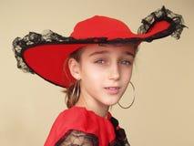 Portrait eines Mädchens im roten Hut und im Kleid mit schwarzer Spitze Lizenzfreies Stockfoto