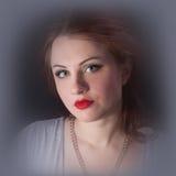 Portrait eines Mädchens mit den roten Lippen in einem grauen Kleid Stockfotos