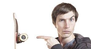 Portrait eines Mannes, der seinem Skateboard zeigt Stockbilder