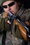 Portrait eines Mannes mit einer Gewehr auf einem Schwarzen. Stockfotografie