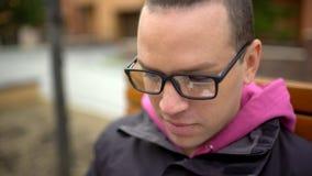 Portrait eines Mannes mit Gläsern Hübsche junge Professioneller, die draußen seinen Laptop an einem sonnigen Tag verwendet Porträ stock video footage