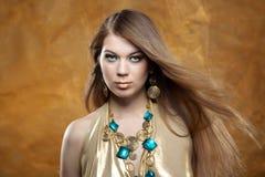 Portrait eines schönen Mädchens in einem Goldkleid Stockbild
