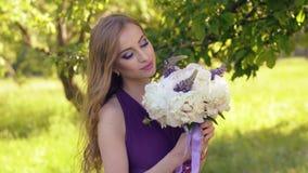 Portrait eines schönen Mädchens mit heller Verfassung Kaukasische Blondine mit einem Blumenstrauß von den Blumen, die aufwerfen u stock video