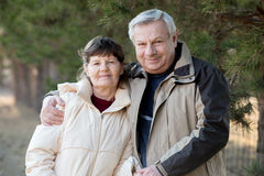 Portrait of elder couple. On a walk in park, senior men hugging his wife with gentleness Stock Photos