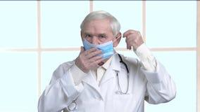 Portrait of elder doctor put on protective blue medical mask. Kind old doctor against big framed windows background stock video