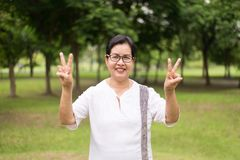Portrait of elderly asian woman wearing glasses hands showing 2 finger at public park,Happy and smiling,Positive attitude thinking. Portrait of elderly asian royalty free stock photography