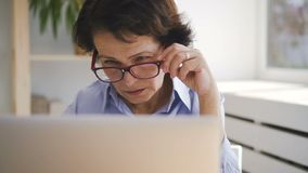 Portrait of elderly business lady sitting in front of laptop screen at home. stock video