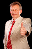 Portrait of elderly businessman. Smiling businessman stretches thumb as a sign of end of successful financial operation Royalty Free Stock Photo