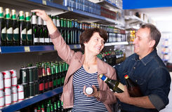 Portrait of an elderly couple buying a beer at the grocery store royalty free stock images
