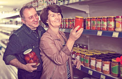Portrait of an elderly couple buying a snacks at the grocery sto royalty free stock images