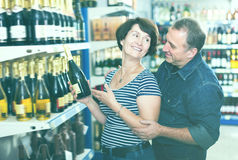 Portrait of an elderly couple buying a wine royalty free stock photo