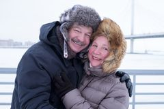 Portrait of elderly couple having fun outdoors in winter. Smiling and looking at camera stock photography