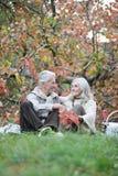 Portrait of elderly couple having a picnic in park stock photos