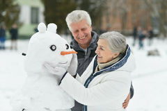 Portrait of elderly couple. Making snowman and shows thumbs up in winter royalty free stock images
