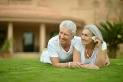 Elderly couple posing  on grass at resort. Portrait of elderly couple posing on grass at resort Stock Images