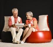 Portrait of elderly couple sitting on armchairs on dark background royalty free stock image