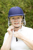 Portrait of an elderly female cricketer adjusting helmet. Portrait of an elderly woman cricketer wearing a batswomans' safety helmet Adjusting the chin strap for royalty free stock photo