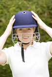 Portrait of an elderly female cricketer adjusting helmet. Portrait of an elderly woman cricketer wearing a batswomans' saftey helmet royalty free stock photo