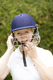 Portrait of an elderly female cricketer. Portrait of an elderly woman cricketer wearing a batswomans' safety helmet Adjusting the helmet strap for a comfortable royalty free stock photography