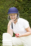 Portrait of an elderly female cricketer. Portrait of an elderly woman cricketer wearing a batswomans' safety helmet and holding a ball stock images