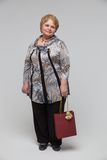 Portrait of an elderly happy woman on a grey Royalty Free Stock Photography