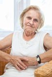 Portrait of an elderly lady sitting in a chair Stock Photography