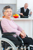 Portrait elderly lady in wheelchair husband cooking Royalty Free Stock Image