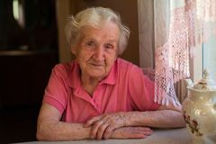 Portrait of an elderly lone woman in her house. stock photos