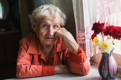 Portrait of elderly lone woman near window in the house. Royalty Free Stock Photos