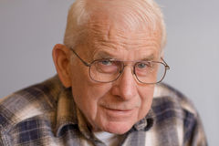 Portrait of elderly man. Portrait of a man nearly 86 years old.  He has white hair and blue eyes and wears eyeglasses and a plaid shirt.  He has direct eye Stock Photography