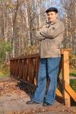 Portrait of elderly man in black hat in wood Stock Photo