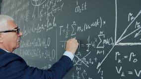 Portrait of elderly man college teacher underlining formula on chalkboard writing
