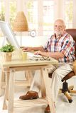 Portrait of elderly man with computer. Portrait of elderly man sitting at desk using desktop computer, smiling at camera royalty free stock image
