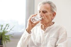Portrait elderly man drinking water Stock Photography