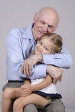 Portrait of an elderly man embracing a granddaughter Royalty Free Stock Photos