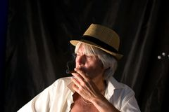 Portrait of an elderly man with gray hair, wearing a straw hat on a black background Royalty Free Stock Images