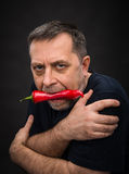 Elderly man with red pepper in his mouth Stock Images