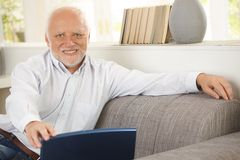 Portrait of elderly man sitting on sofa. Holding laptop computer, smiling happily at camera Stock Image