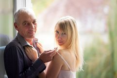 Portrait of Elderly Man Standing near the Window with His Young Blonde-haired Wife in Summer Short Dress. Couple with. Age Difference Stock Photography
