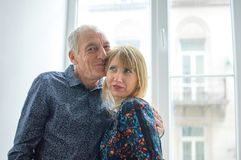 Portrait of Elderly Man Standing near the Window with His Young Blonde-haired Wife in Warm Dress. Couple with Age. Difference royalty free stock image