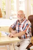 Portrait of elderly man in study at home. Portrait of elderly man sitting in study at home, smiling at camera stock image