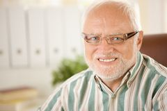 Portrait of elderly man wearing glasses. Closeup portrait of elderly man wearing glasses, smiling at camera royalty free stock photo