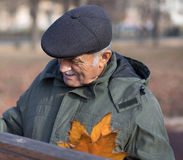 Portrait of elderly man with white hair and beret on his head. Royalty Free Stock Images