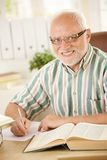 Portrait of elderly man working at desk. Portrait of smiling elderly man working at desk, taking notes, using books Stock Image