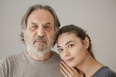 Portrait elderly man with young woman on gray background stock photography