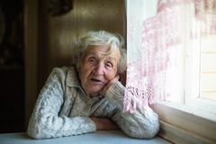 Portrait of an elderly pensioner woman in his house. Portrait of an old elderly pensioner woman in his house royalty free stock image
