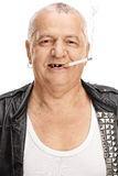 Portrait of an elderly punker with a cigarette. Isolated on white background royalty free stock photography