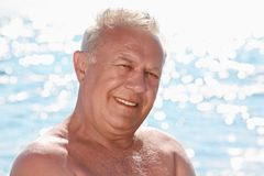 Portrait of elderly smiling man on seacoast Stock Photos